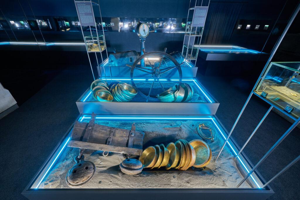 """Elementy ładunku, urządzenia i fragmenty konstrukcji z zatopionych statków na wystawie """"Do DNA…"""" w Spichlerzach na Ołowiance."""