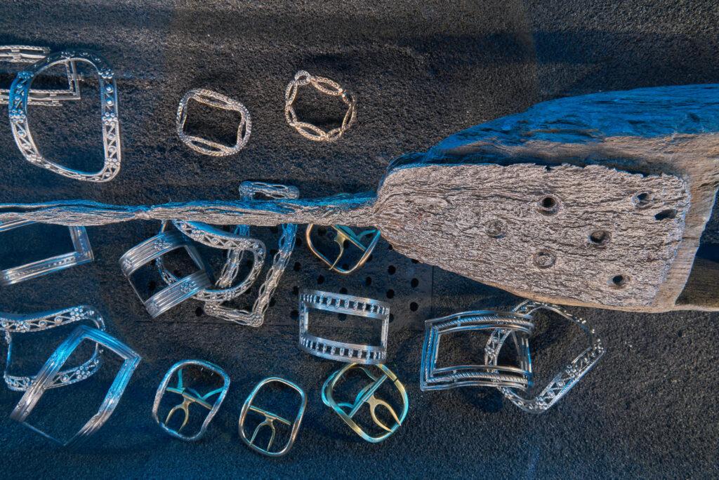 """08. Fragment pompy zęzowej oraz ozdobne sprzączki do butów, odkryte w XVIII-wiecznych wrakach, na wystawie """"Do DNA…"""" w Spichlerzach na Ołowiance."""