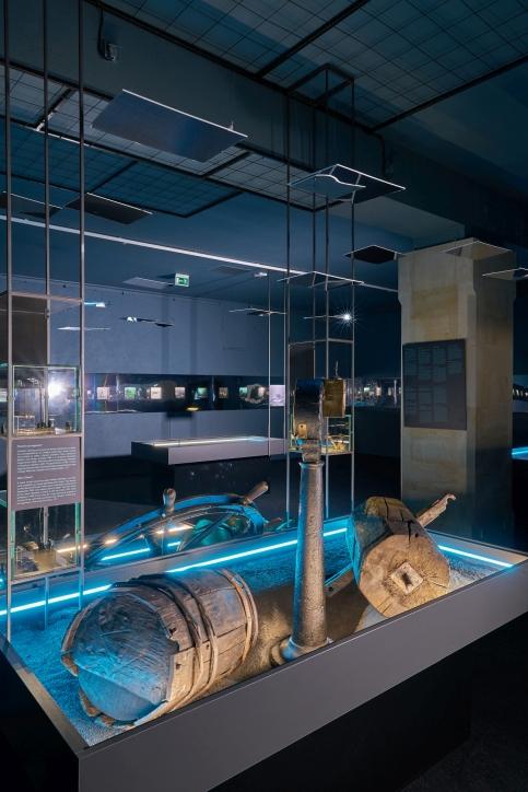 """Fragment wystawy """"Do DNA"""". Na pierwszym planie beczka z wraku średniowiecznego statku handlowego nazwanego Miedziowcem, fot. Dariusz Kula Images"""