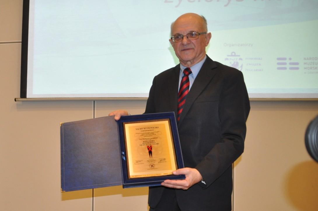 Dyrektor Jerzy Litwin prezentuje dyplom, w którym Yacht Klub Polski przyznaje Mariuszowi Zaruskiemu godność komandora honorowego
