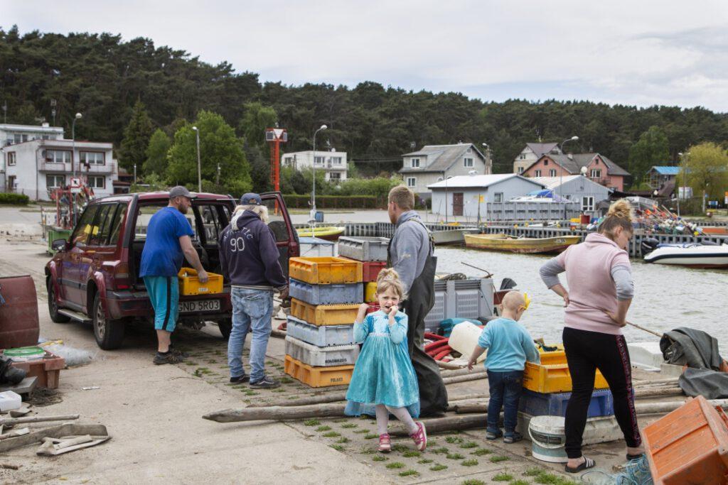 Rybacy i ich rodziny podczas rozładunku ryb w porcie w Piaskach
