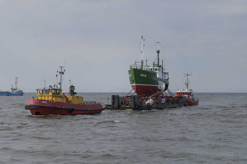 Rozpoczęcie wprowadzenia barki z kutrem GDY-18 do kanału portowego w Łebie