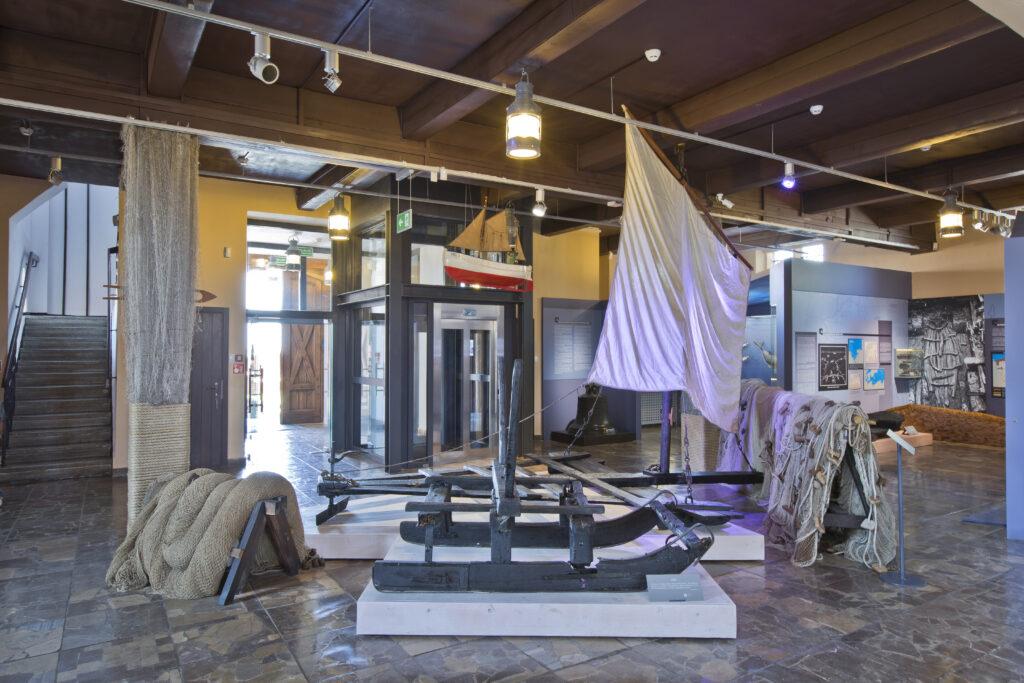 Fragment wystawy Muzeum Rybołówstwa w Helu z zabytkowymi saniami do transportu narzędzi do połowów podlodowych.